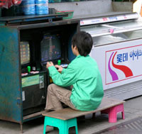 boy playing a street-side video game in Seoul