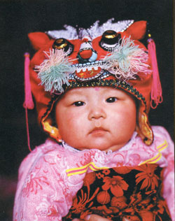 Chinese baby wearing an embroidered hat