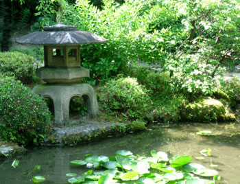 stone lantern by the edge of a pond in Heian Jingu garden
